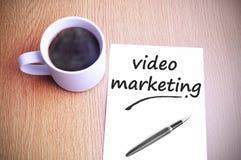 Café en la tabla con el márketing video de la escritura de la nota Imágenes de archivo libres de regalías