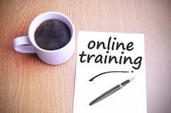 Café en la tabla con la nota que escribe el entrenamiento en línea Imagen de archivo libre de regalías