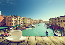 Café en la tabla y Venecia en tiempo de la puesta del sol Imagen de archivo