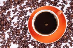 Café en la taza anaranjada rodeada con los granos de café Imagen de archivo libre de regalías