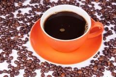 Café en la taza anaranjada rodeada con los granos de café Foto de archivo