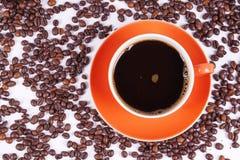 Café en la taza anaranjada rodeada con los granos de café Imagenes de archivo