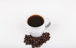 Café en la taza blanca con las habas Foto de archivo libre de regalías