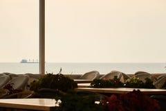 Café en la terraza cerca del mar en puesta del sol imagenes de archivo