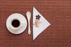 Café en mantel con los granos de café Imagenes de archivo