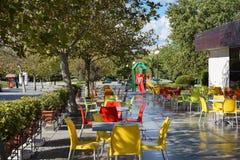 Café en parc, à tables colorées et chaises Photographie stock