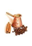 Café en pote del café turco del cobre del vintage (cezve o ibrik), granos de café y palillos de canela en blanco imagenes de archivo