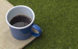 Café en taza azul de la lata en fondo de la hierba foto de archivo