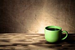 Café en taza en la tabla de madera enfrente de un backgr defocused de la arpillera Foto de archivo