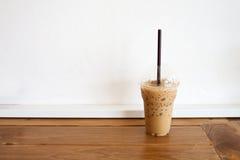 café en taza plástica en la tabla de madera Fotografía de archivo libre de regalías