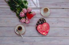 Café en tazas, rosas y una caja de chocolates en una tabla de madera Fotos de archivo libres de regalías