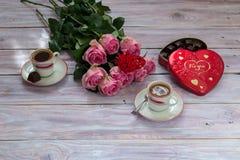 Café en tazas, rosas y una caja de chocolates en una tabla de madera Fotos de archivo
