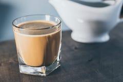 Café en un fondo azul de la pizca de cristal foto de archivo