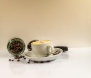 Café en una taza blanca con un tarro caido de granos y de puerto de café Imágenes de archivo libres de regalías