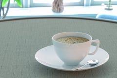 Café en una taza en la tabla por la ventana stock de ilustración