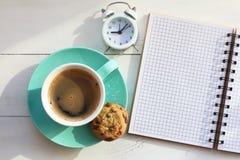 Café en una taza y galletas de la turquesa cerca de un cuaderno en una tabla blanca y el despertador blanco la visión superior foto de archivo