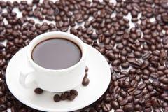 Café en una taza y granos de café Fotografía de archivo libre de regalías