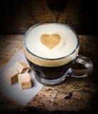 Café en verre avec la mousse de coeur et sucre de canne sur le vieux Ba en bois Photo stock
