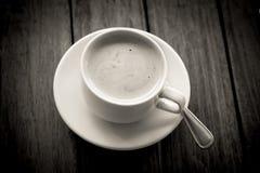 Café en verre sur de table la couleur arrière et blanche en bois dedans Photo libre de droits
