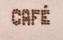 Café escrito com os feijões de café na lona Fotografia de Stock Royalty Free