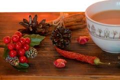 Café, especias y conos del pino en un fondo de madera Concepto de la Navidad Una taza de café caliente con leche, canela y el chi foto de archivo