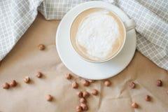 Café et écrous chauds de matin sur le papier de métier photographie stock