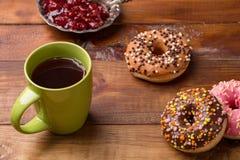 Café et beignet beignet avec une tasse de thé sur un fond en bois foncé photos libres de droits