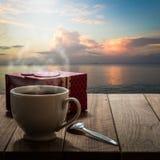 Café et boîte-cadeau chauds sur la table en bois avec le paysage marin Photographie stock libre de droits