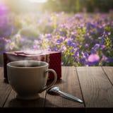 Café et boîte-cadeau chauds sur la table en bois dans le pré Photographie stock libre de droits