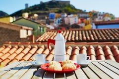 Café et bonbons italiens avec la vue au village de Bosa, Sardaigne, Italie Image stock