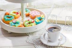 Café et butées toriques avec la décoration colorée sur la table blanche Image stock
