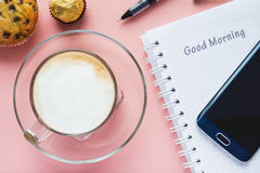 Café et carnet et un téléphone sur une table rose Image stock