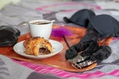 Café et dessert doux sur un linge de lit Instruments et sous-vêtements érotiques dans la chambre à coucher images stock