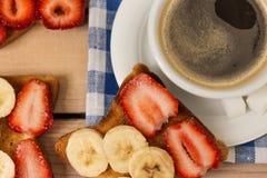 Café et pain grillé avec des fraises et des bananes Photo stock