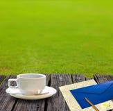 Café et papier de lettre chauds sur la table en bois Photographie stock libre de droits