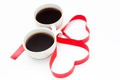 Café et ruban rouge sur le fond en bois blanc Image stock