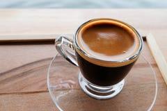 Café express caliente en taza y platillo de cristal claros en la bandeja de madera Imagenes de archivo