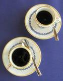 Café express fuerte, caliente en tazas decorativas y platillos Fotos de archivo