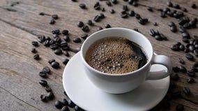 Café express oscuro caliente de la taza de café y del grano de café en la tabla de madera almacen de video