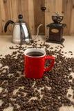 Café express que fuma en taza roja con los granos de café y el café viejo milipulgada imagen de archivo