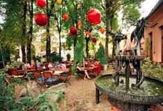 Café exterior com os povos que relaxam sob lâmpadas de rua Fotos de Stock
