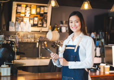 Café femelle asiatique de tablette de prise de tablier de treillis d'usage de barman images libres de droits