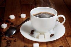 Café fresco caliente en una taza blanca con el azúcar Imagenes de archivo