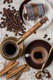 Café fresco con el canela, accesorios del café en la tabla blanca vieja Foto de archivo libre de regalías