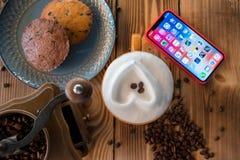 Café fresco con smartphone y con los granos de café en una tabla de madera Fotos de archivo libres de regalías
