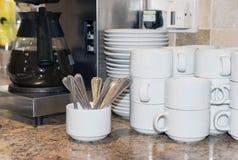 Café fresco, copos limpos, colheres e pires Foto de Stock Royalty Free