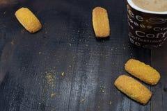 Café fresco de la mañana con leche y galletas de torta dulce deliciosas en una opinión de sobremesa oscura Imagen de archivo