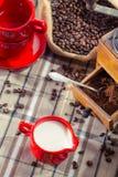 Café fresco del leche y molido en la amoladora Imagen de archivo libre de regalías