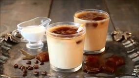 Café frio congelado do latte com cubos de gelo e feijões de café A mão da mulher põe nas palhas de papel de um cocktail de vidro filme