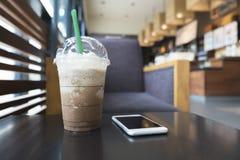 Café frio do freppe do mocha e telefone celular branco na mesa de centro dentro fotografia de stock royalty free